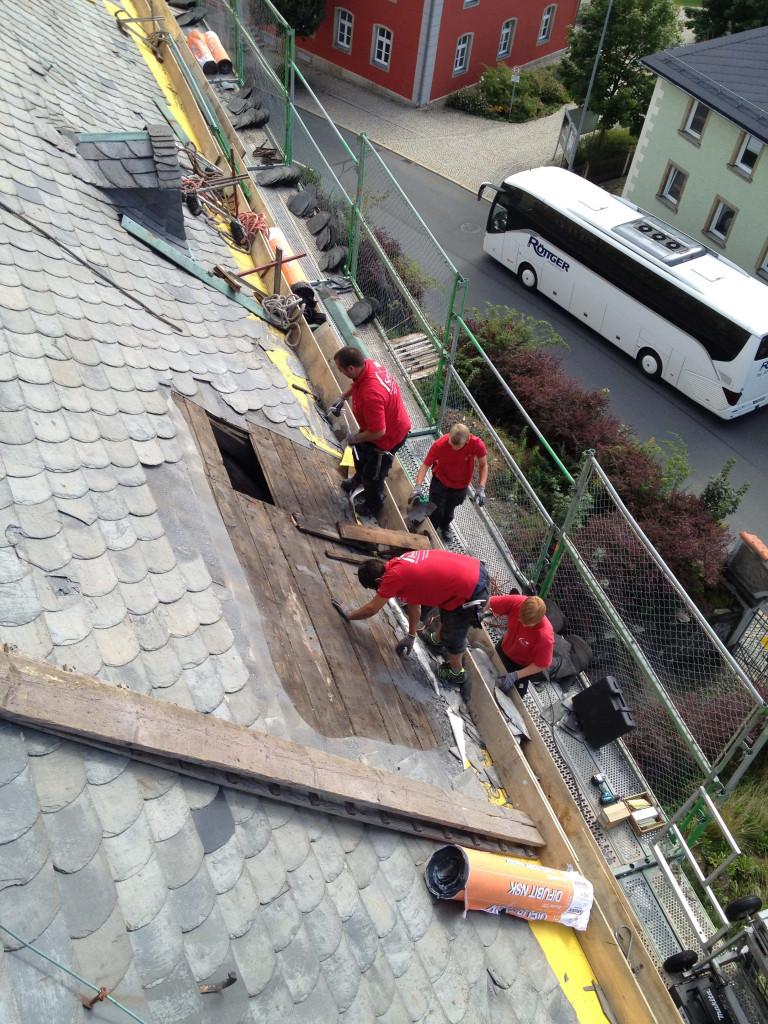 Dachdecker bei der Arbeit am Kirchenschiff